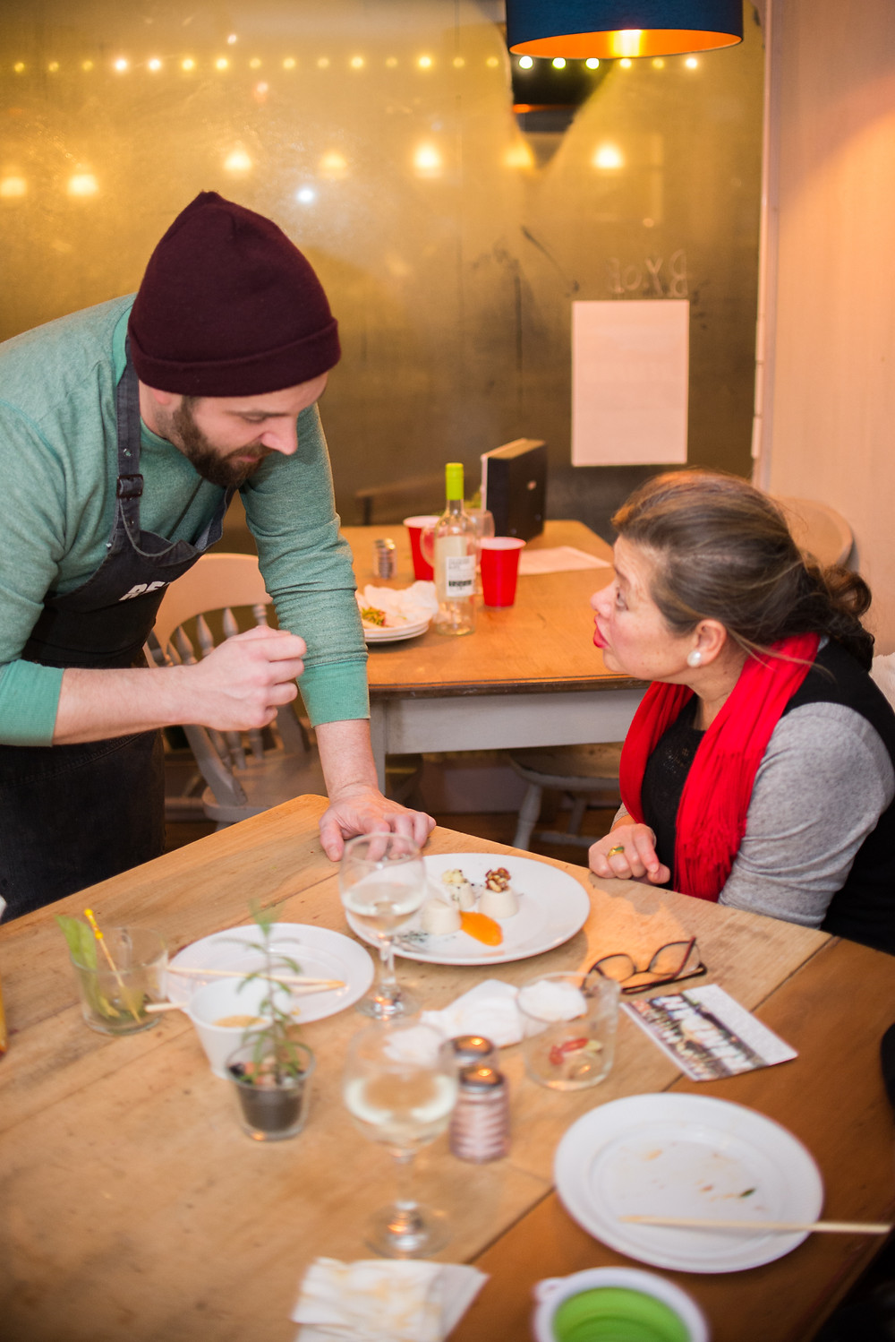 Rempah's chef George talking to a guest about his plate of vegan cheesecake.