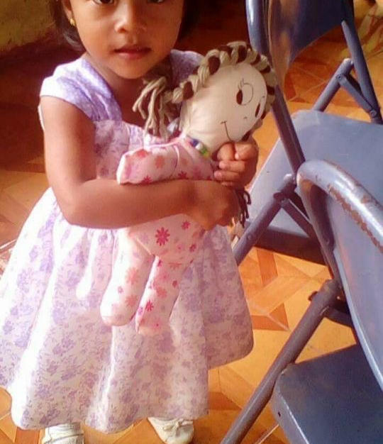Toddler Holding Salvation Doll
