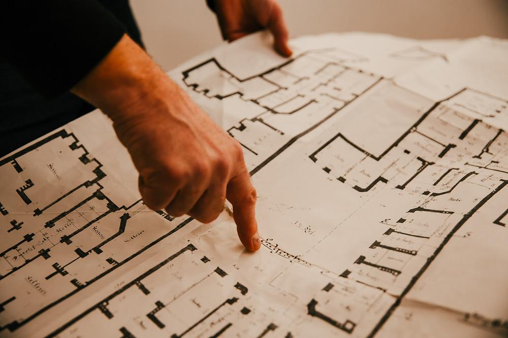 Landlord flips through copy of original apartment plan in Moabit, Berlin.