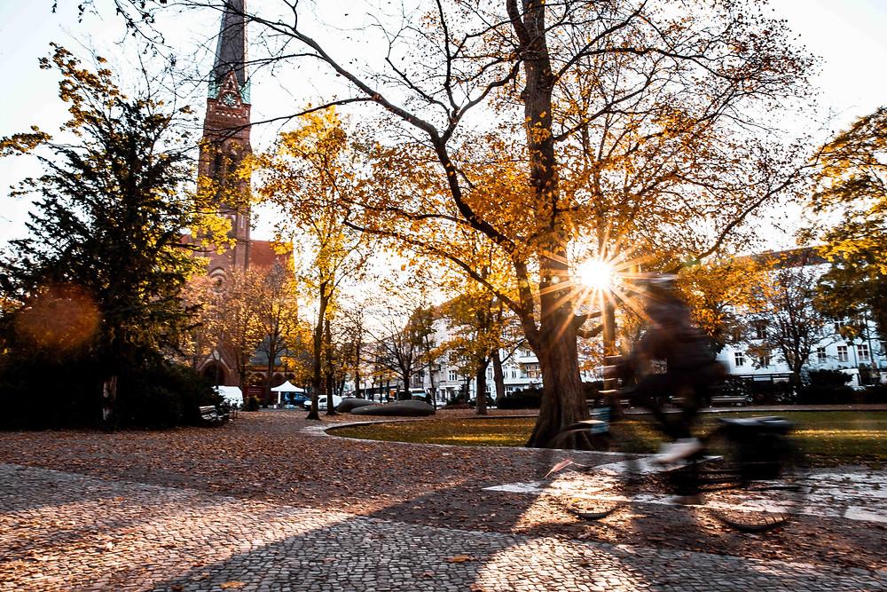 Morning sun on church as biker speeds by in Moabit, Berlin.