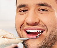 man smiling with dental mirror