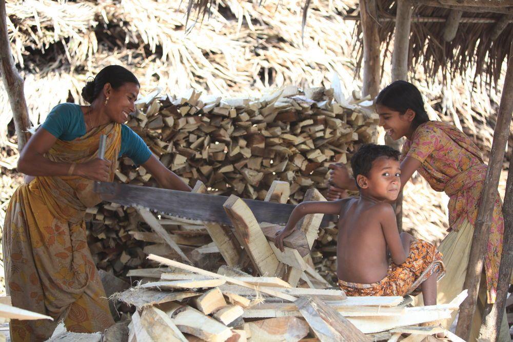 Uma mãe e sua filha compartilham um sorriso enquanto trabalham na serralheria.