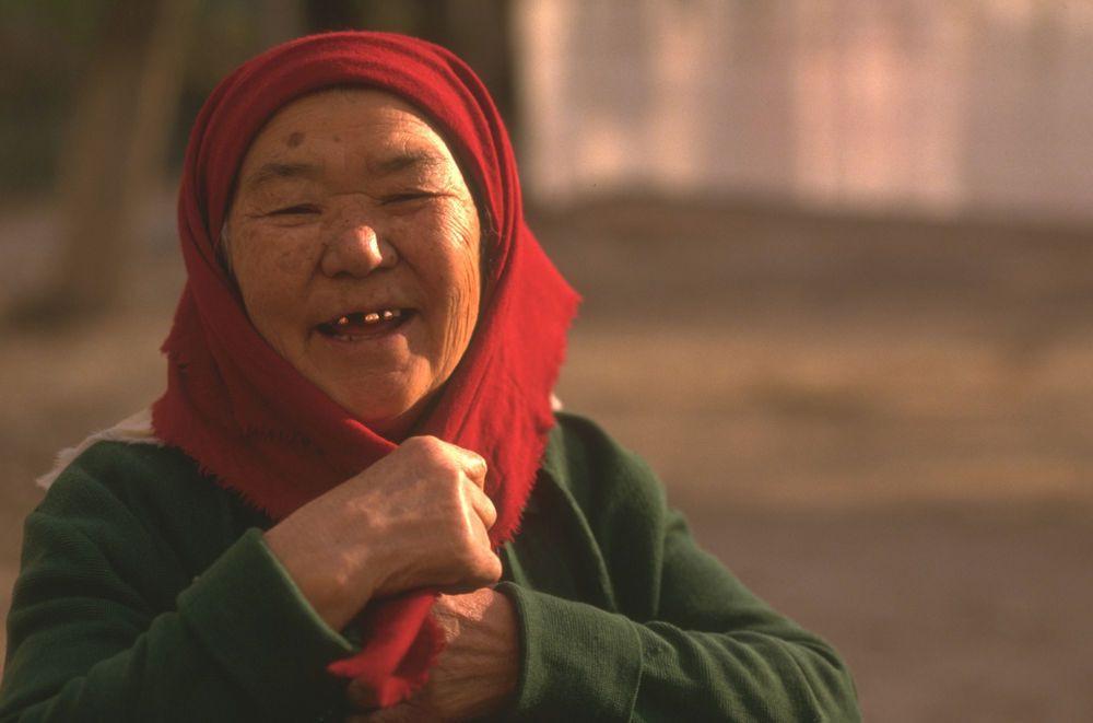 Idosa da Ásia Central sorrindo para a câmera