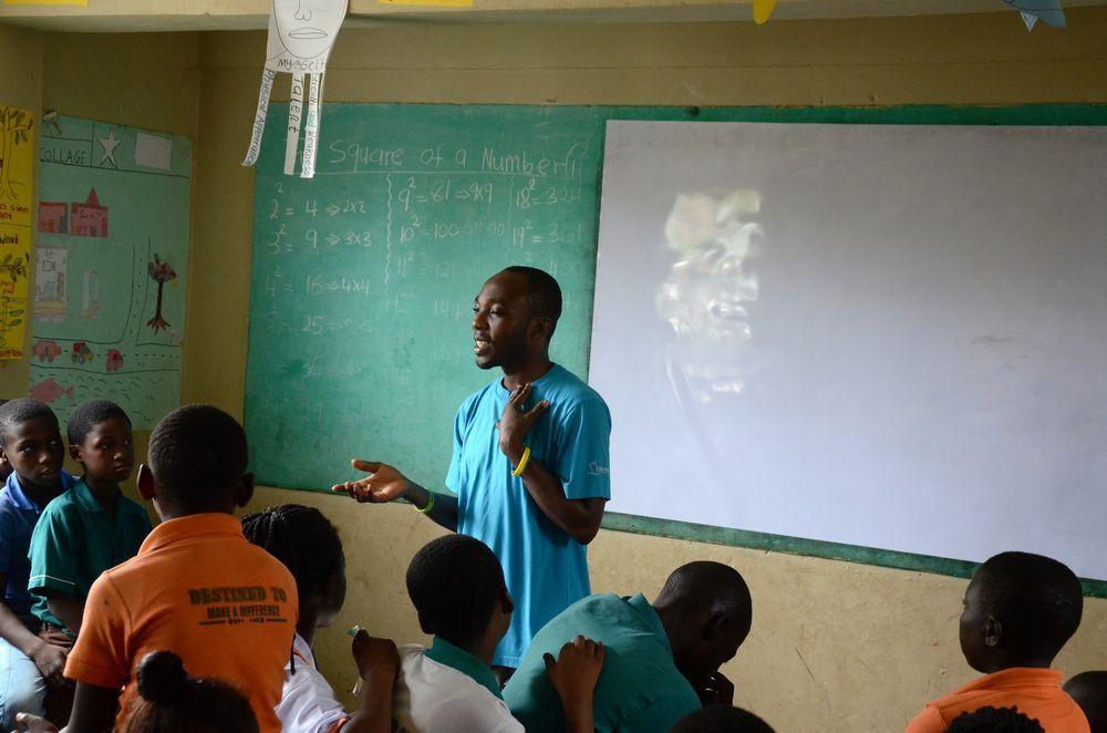 Godfred falando a crianças na escola primáriag to kids at P&G School in Kumasi, Ghana