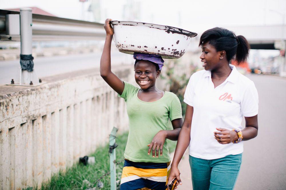 """Portia, uma missionária de Gana, caminhando com uma das meninas """"Kayeye"""""""