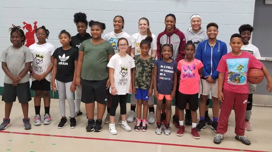 Children from the Southern Maryland HEAT Athletic Program pose with Univerisity of Massachusets guard Jessica George