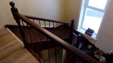Лестница на тетивах с поворотом на 180 градусов, угловыми ступенями, кованными балясинами, обшивкой
