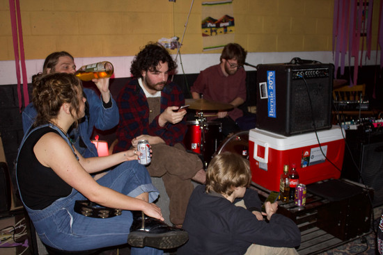 Cole Gorden, Rob Cormier and other attendees sit on the stage as Gozen finishes setting up. Gorden and Cormier are known for their liquid light shows at other house shows.