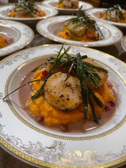 Seared Scallop over Brown Butter Sage Sweet Potato Mash in Pomegrante Gastrique topped w/ Fried Leeks