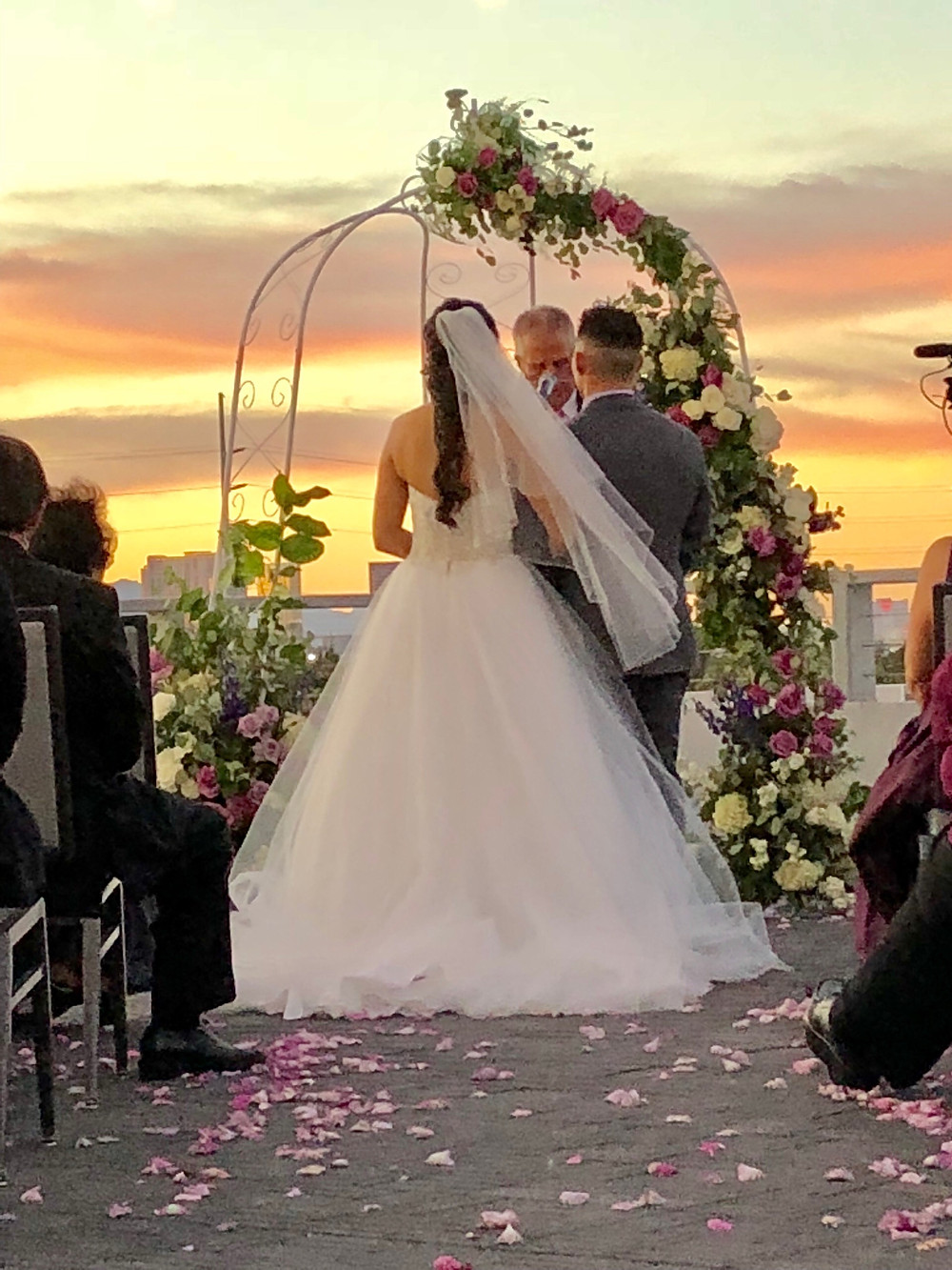Bride and Groom in front of floral arch agains Vegas sunset