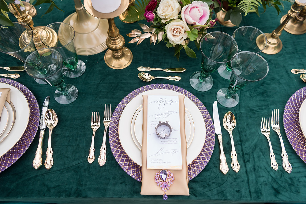 A table set with gold accents, luxurious flowers, green velvet tablecloth