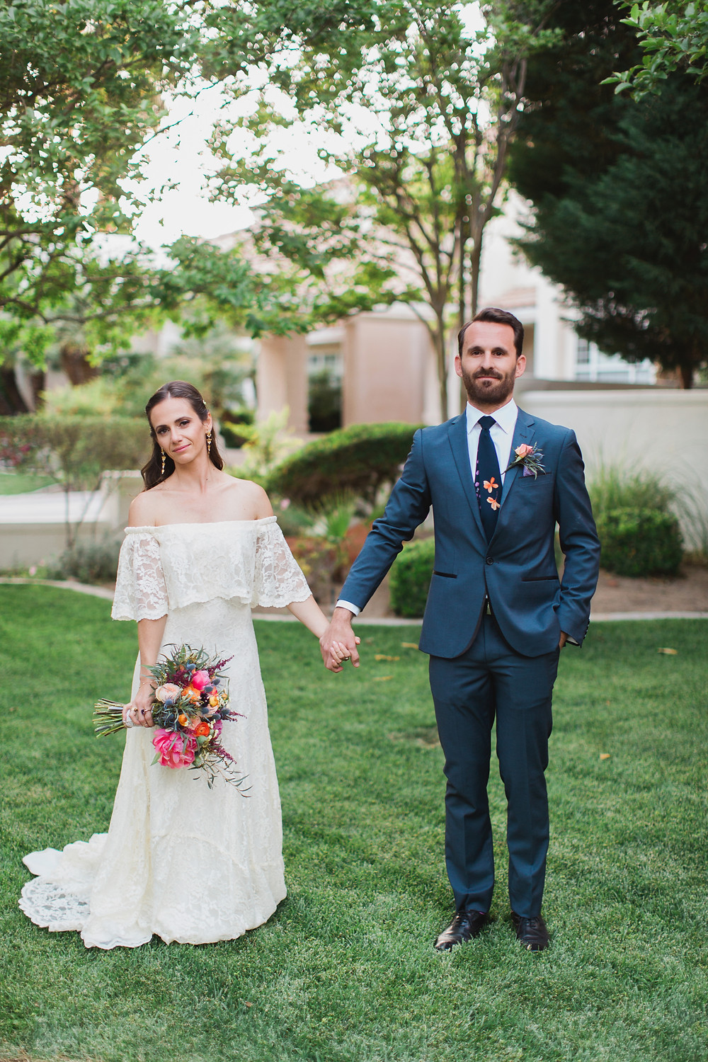 Bride and Groom hold hands at their backyard boho wedding