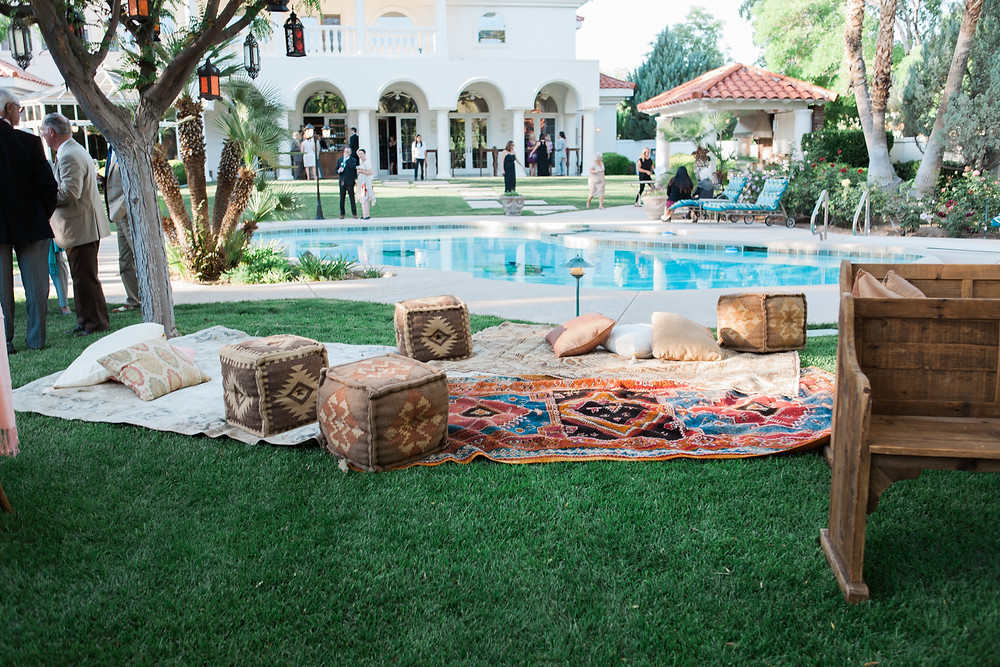 A backyard boho wedding features comfy blankets, pillows and poufs for seating