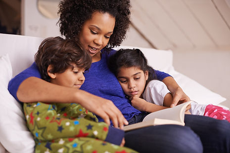 Foster mother and foster children reading a book. Ontario foster care.