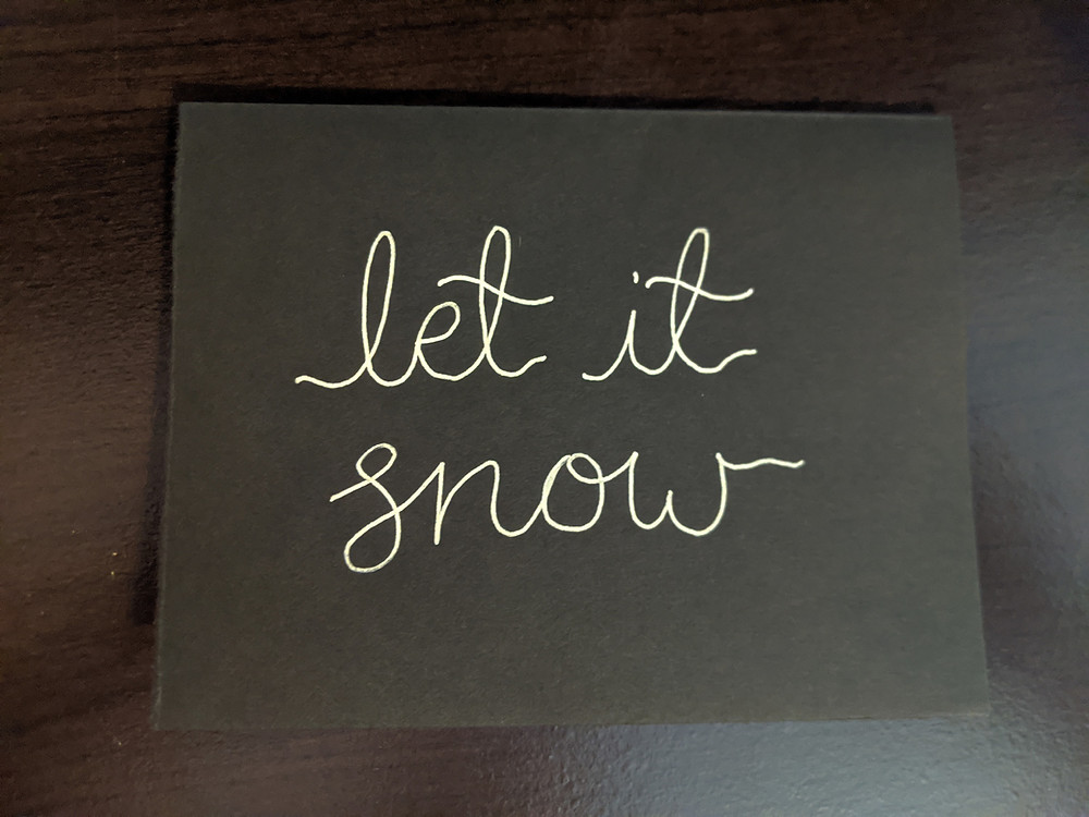 """A DIY christmas card sits on a black desk. It has """"let it snow"""" written on its front in white gel pen."""