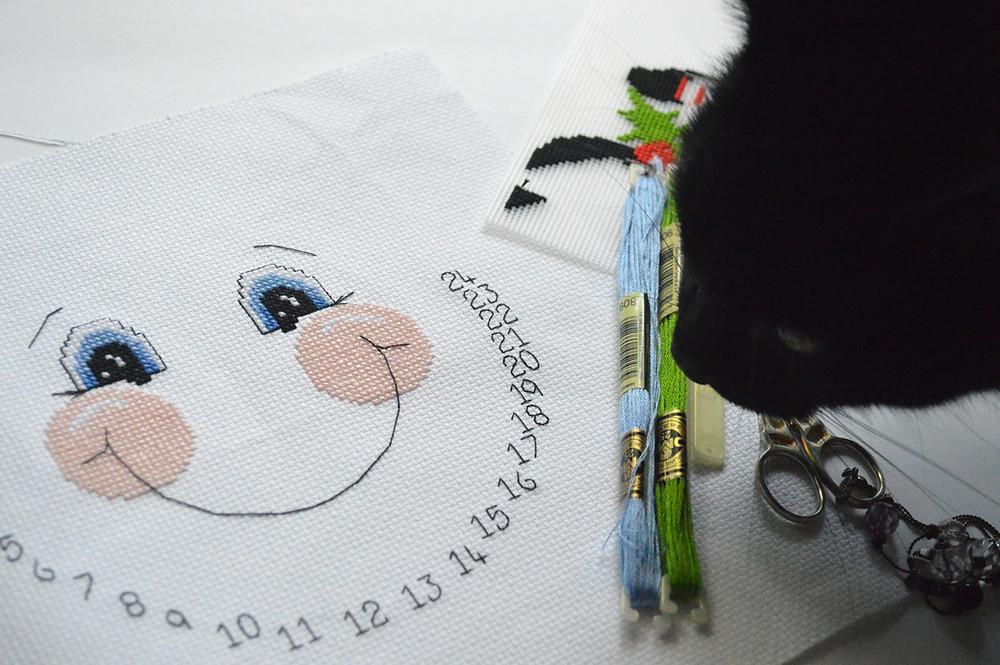 A black cat photobombs a cross stitch design of a snowman.
