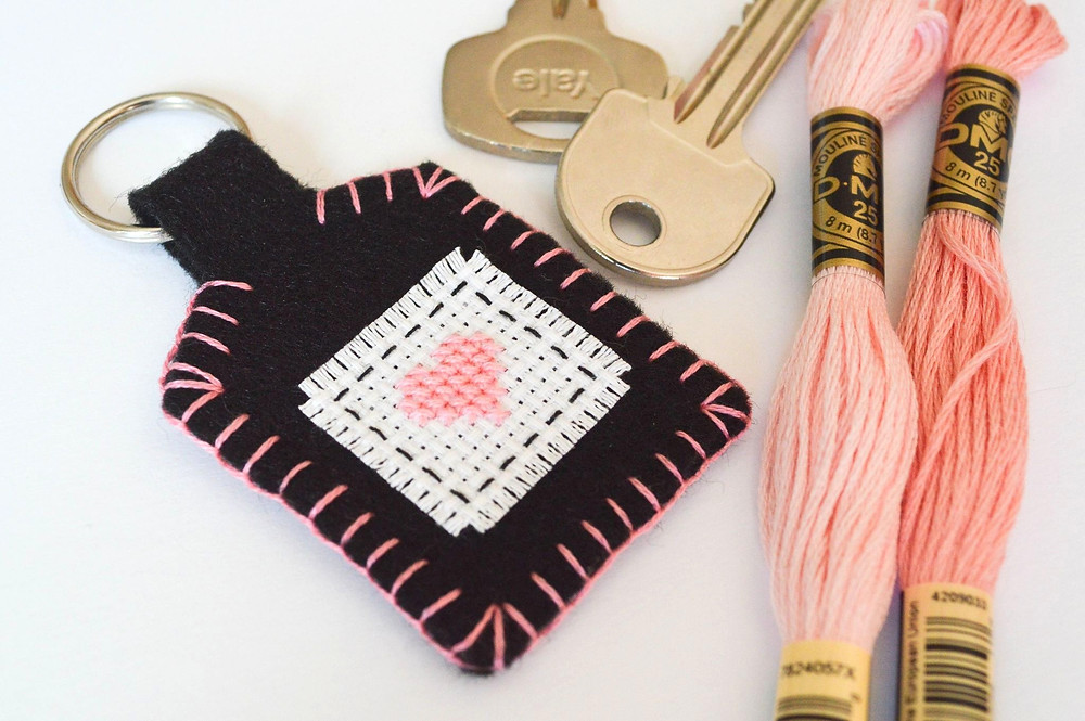 Pink thread sits next to a brown and pink cross stitched keychain.