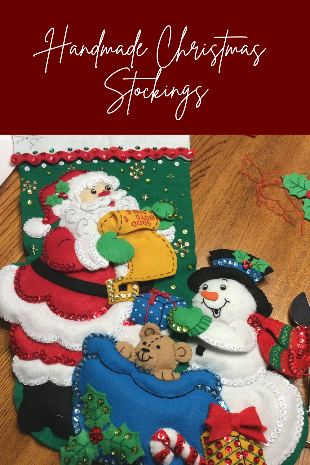 A handmade felt Christmas Stocking lays against a wooden table. The stocking has Santa and a snowman on it.