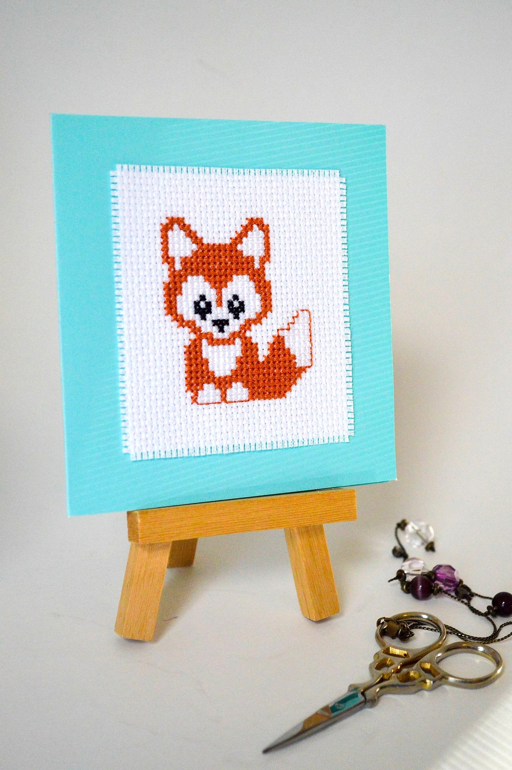 An orange fox is cross stitched onto a blue card.