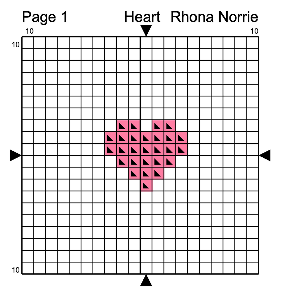 A cross stitched pink heart sits on a graph paper chart.