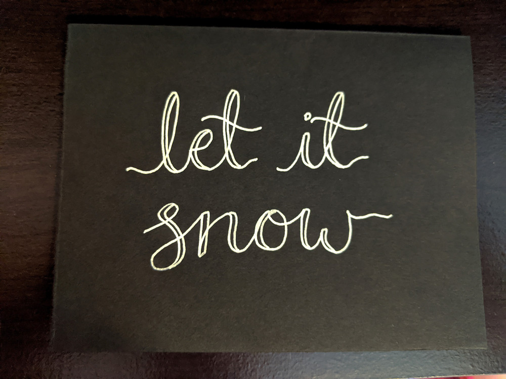 """A black DIY Christmas card lays on a desk. It has thick hand lettering drawn on it using white gel pen, saying """"let it snow""""."""