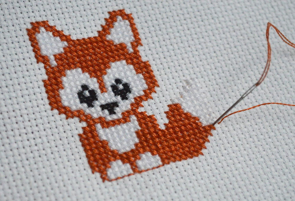 A needle pokes into white fabric right next to a cute stitched orange fox to begin the back stitch outline of the fox's tail.