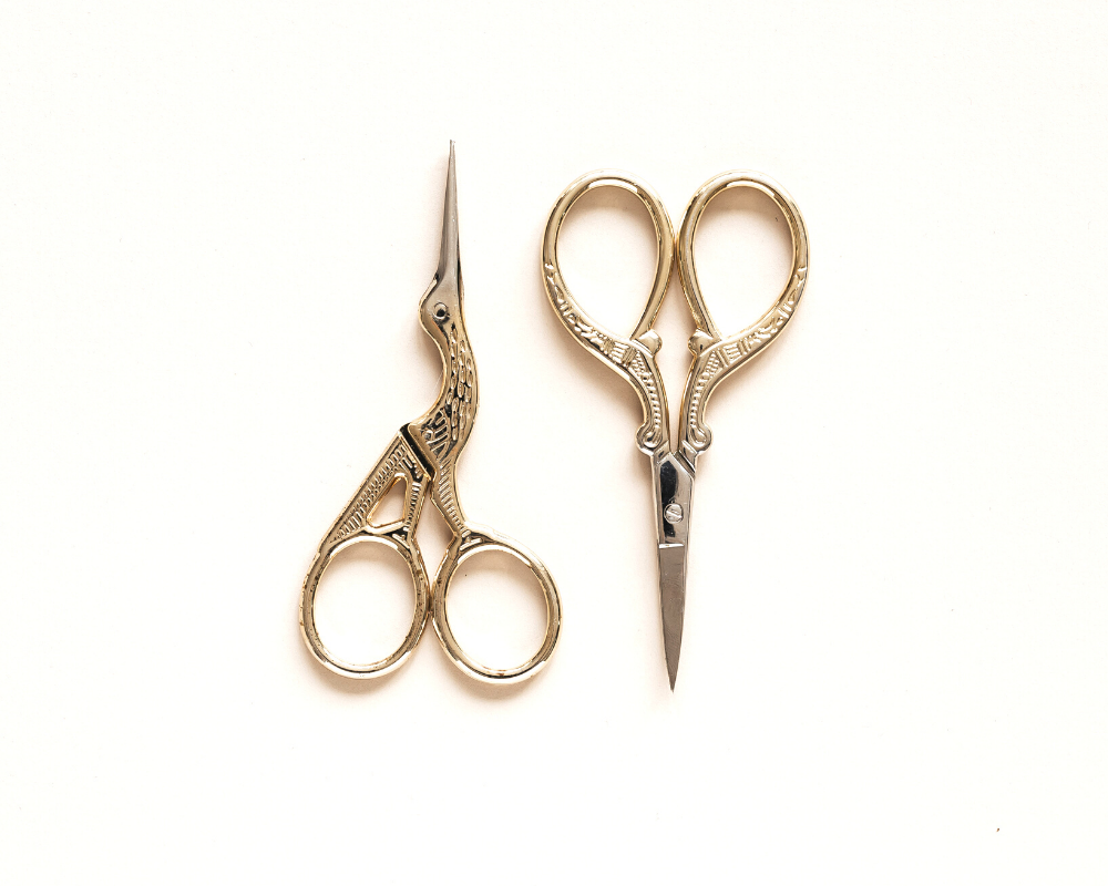 Two gold antique pairs of embroidery scissors.