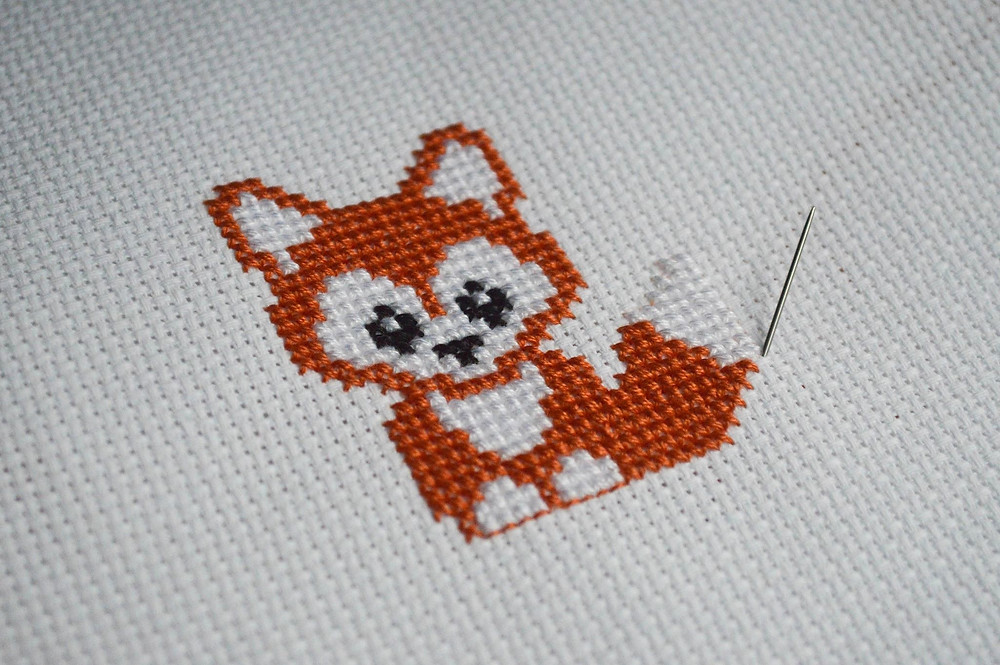 A needle sticks out of fabric next to a stitched orange fox.