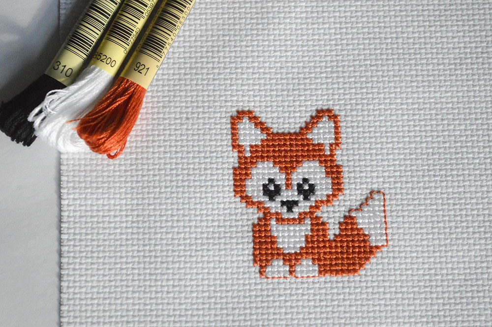 An orange fox is cross stitched into white aida fabric.