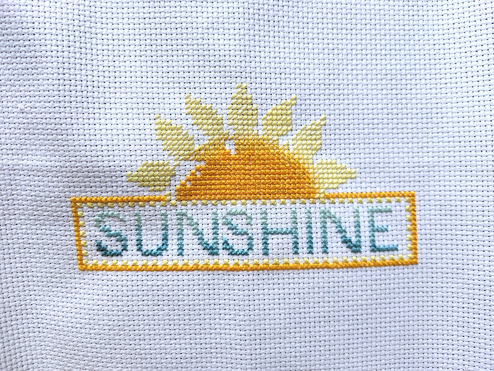 """A blue and yellow cross stitch design with the word """"Sunshine"""" and a flower-like sun."""