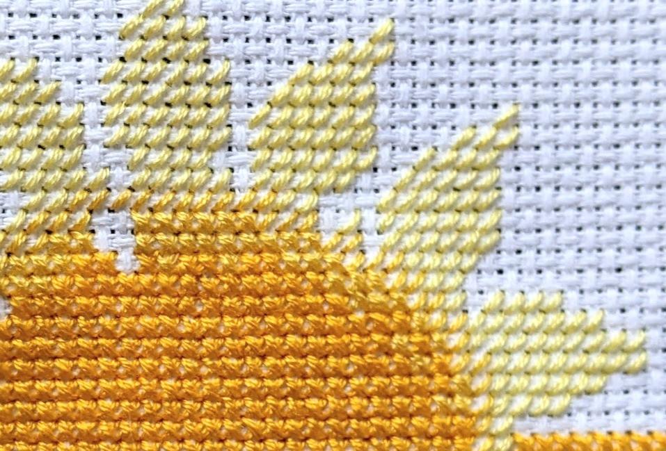 A cross stitched sunshine flower.