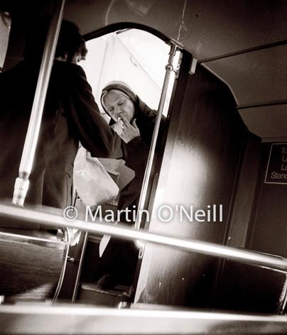Woman lights cigarette on bus.