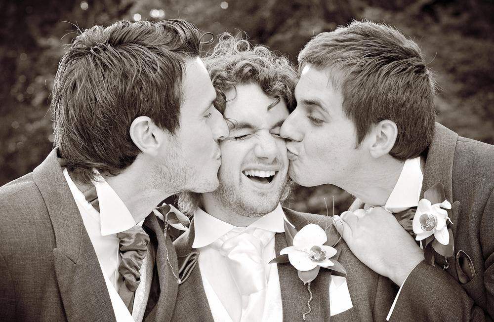 Groomsmen kiss groom, wedding