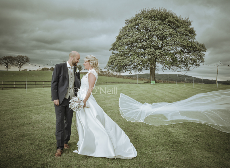 Bride and groom with veil blowing of