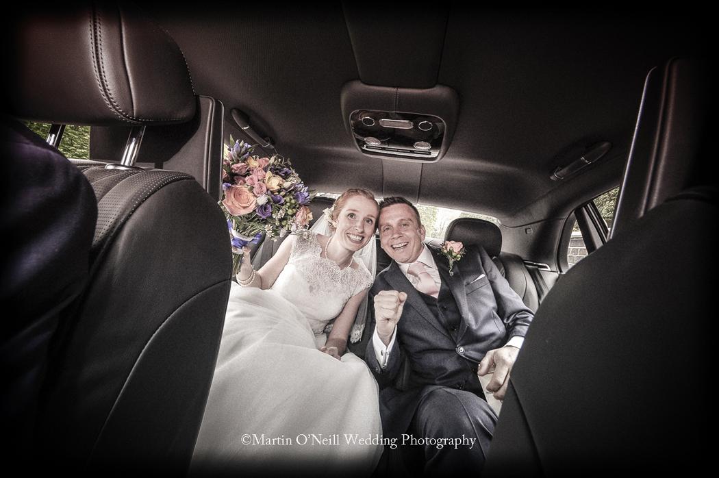 Bride, groom, wedding car