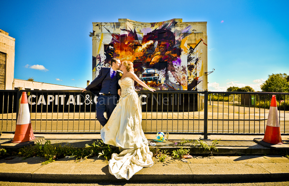 Bride and groom in front of mural