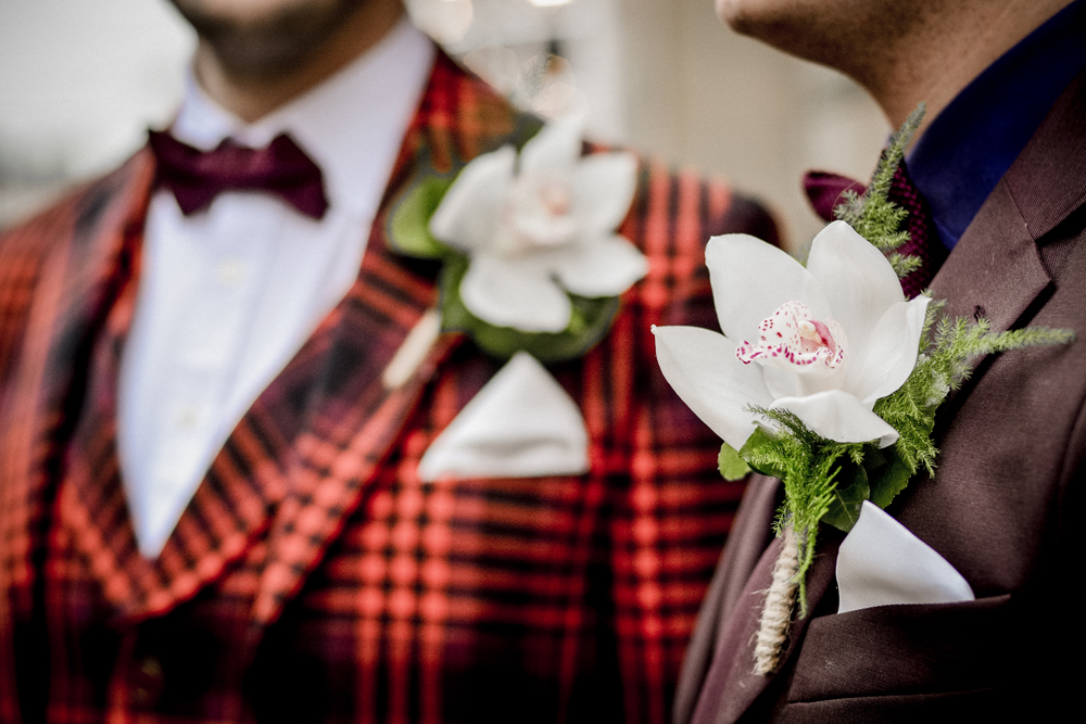 Buttonholes, gay couple in suits