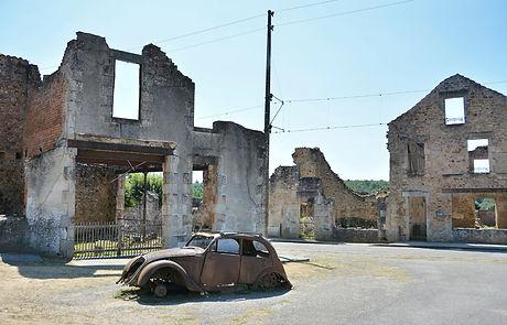 derelict car, burned out buildings