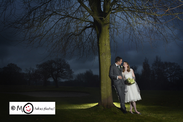Bride and groom by tree in winter