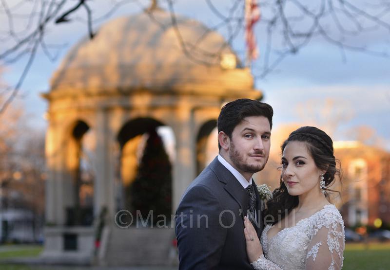 Bride and groom by a gazebo.