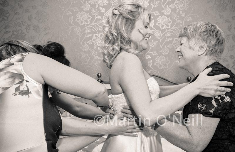 Bride has dress fastened