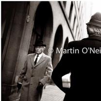 Two men pass in the street in Manchester