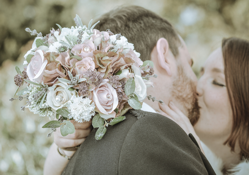 Bride and groom kiss, bouquet