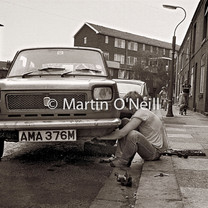 A man fixes a car on a street in Eccles