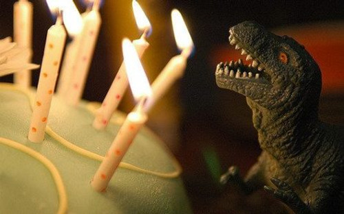 Toy dinosaur facing a cake with lit candles.