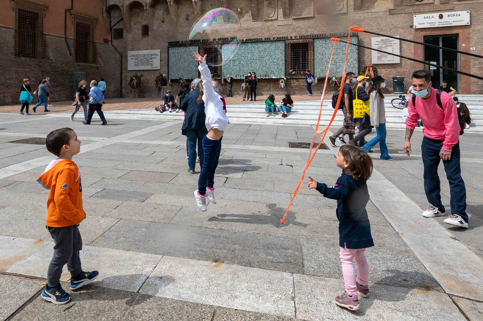 Kids practising 'volley ball' with soap bubbles in Bologna