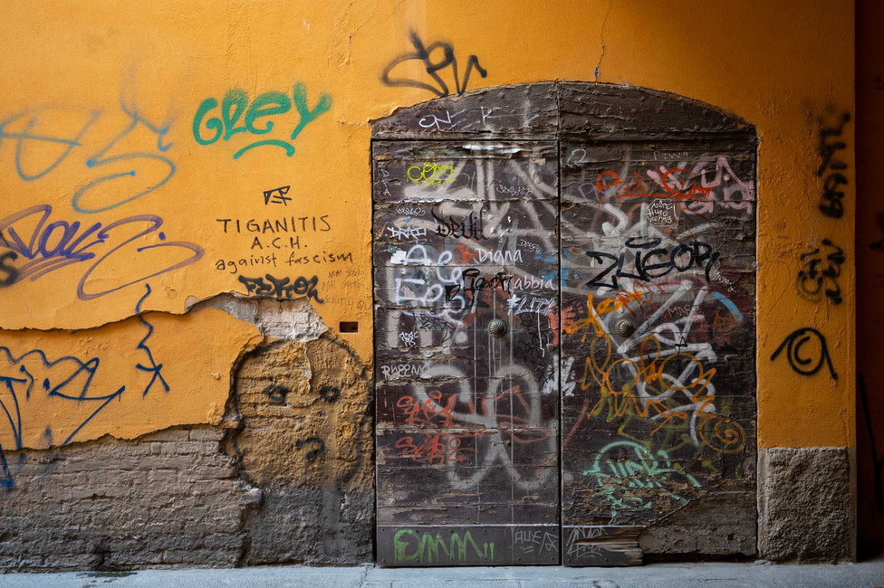 Scribbles on an entrance door in Bologna