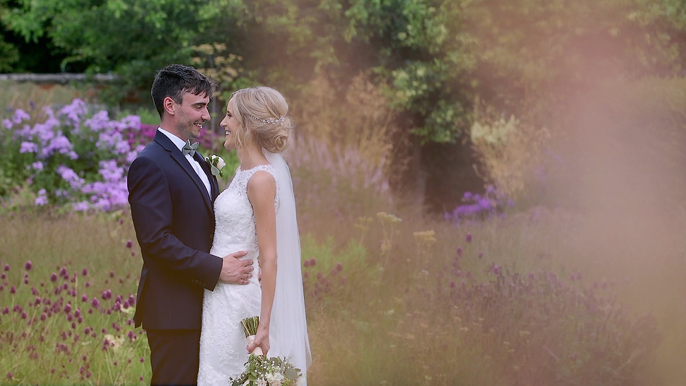 Bride and Groom standing in long grass at Bury Court Barn taken by a wedding videographer