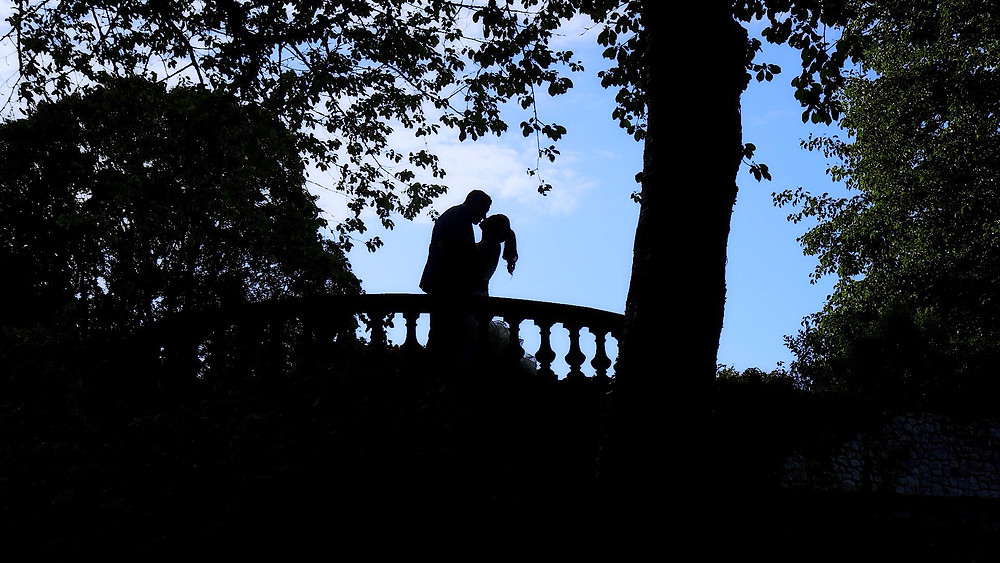 bride and groom kissing on a bridge at their micro wedding