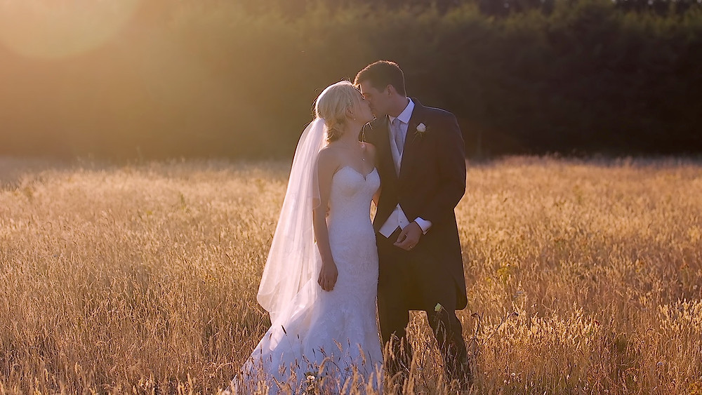 bride and groom standing in corn field kissing during their micro wedding